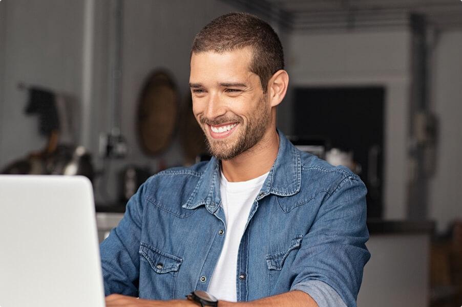 Man in denim shirt smiling and using macbook computer